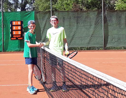 2 Jungen geben sich die Hand über ein Tennisnetz hinweg