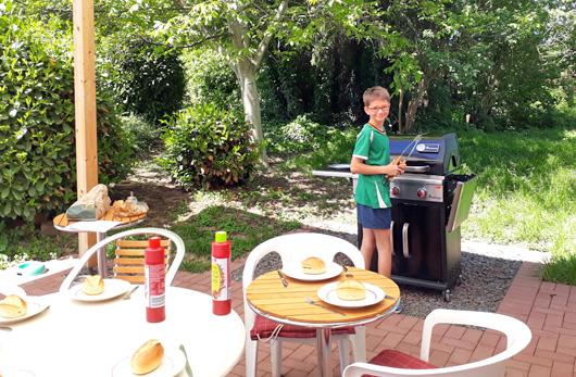 ein Junge steht mit einer Grillzange vor einem grill