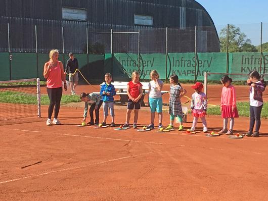 Kinder in einer Reihe auf einem Tennisplatz stehend