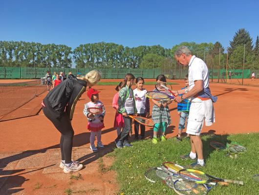 Eine Gruppe kinder vor einem Tennis Trainer