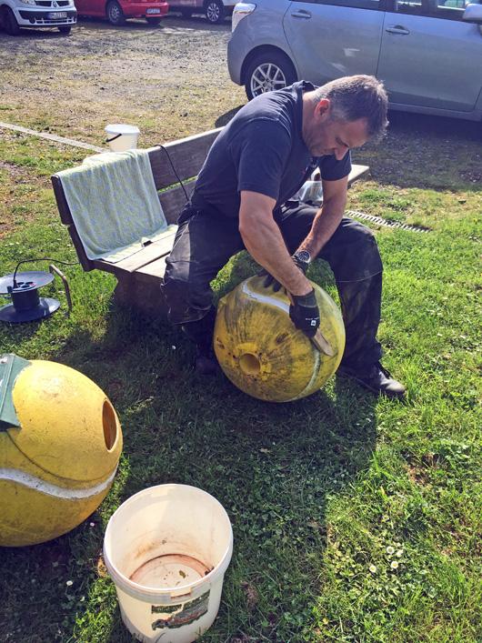 Ein Mann reinigt übergroße Tennisbälle mit einer Bürste