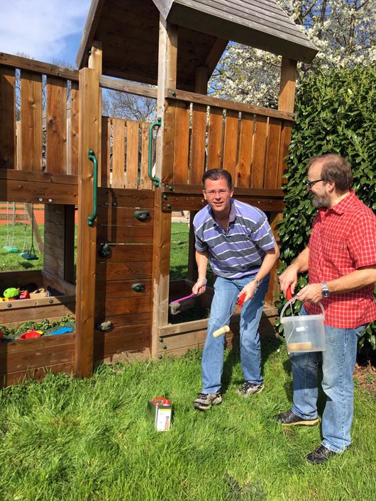 2 Männer streichen ein Kinderspielgerät mit Holzschutzfarbe