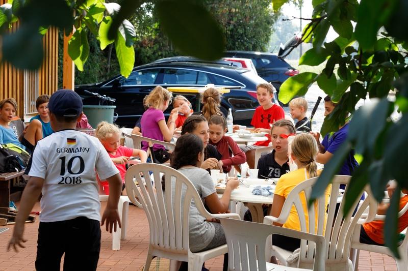 Mehrere Kinder beim Essen an einem weißen Tisch