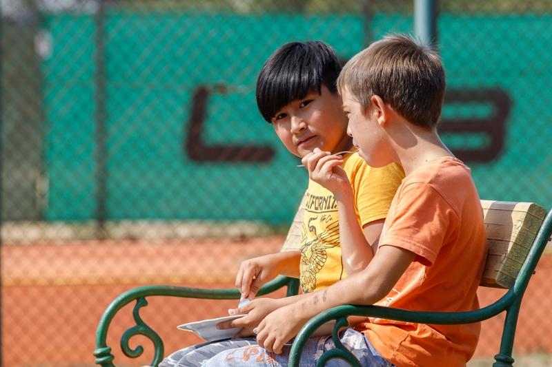 2 Kinder essen auf einer Bank