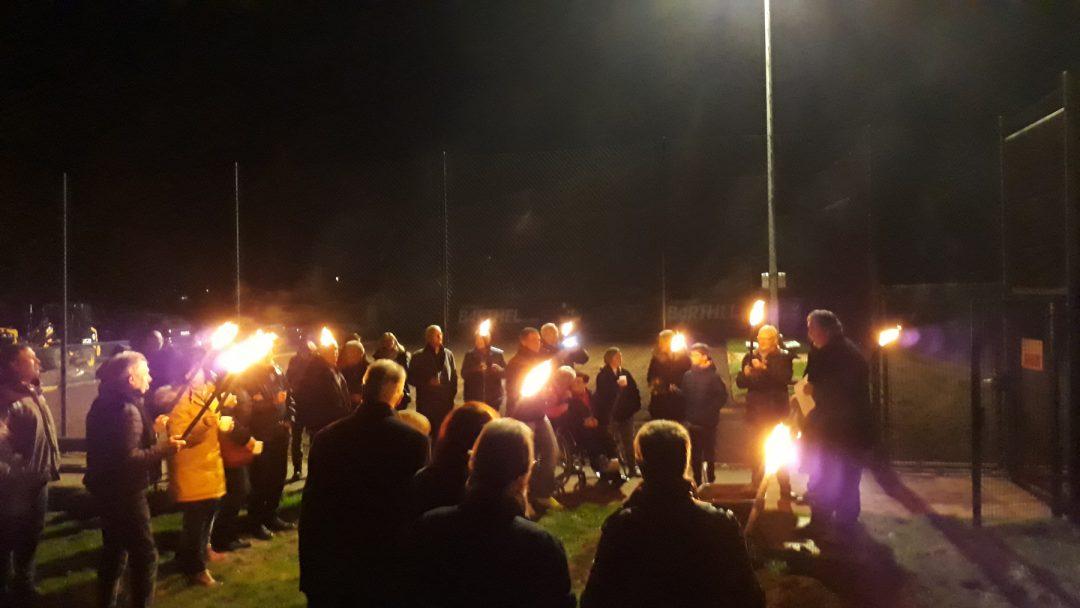 Eine Gruppe Menschen mit Fackeln im dunkeln auf einem Tennisplatz