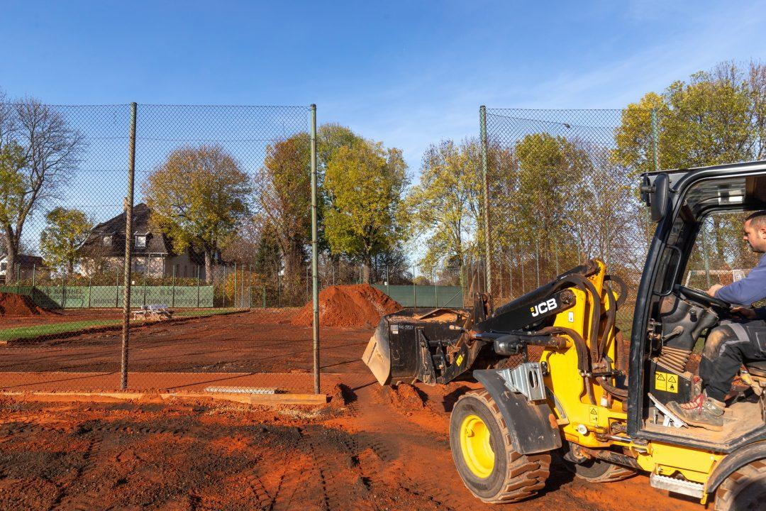 Ein Tennisplatz befindet sich im Bau mit mehreren Sandhaufen