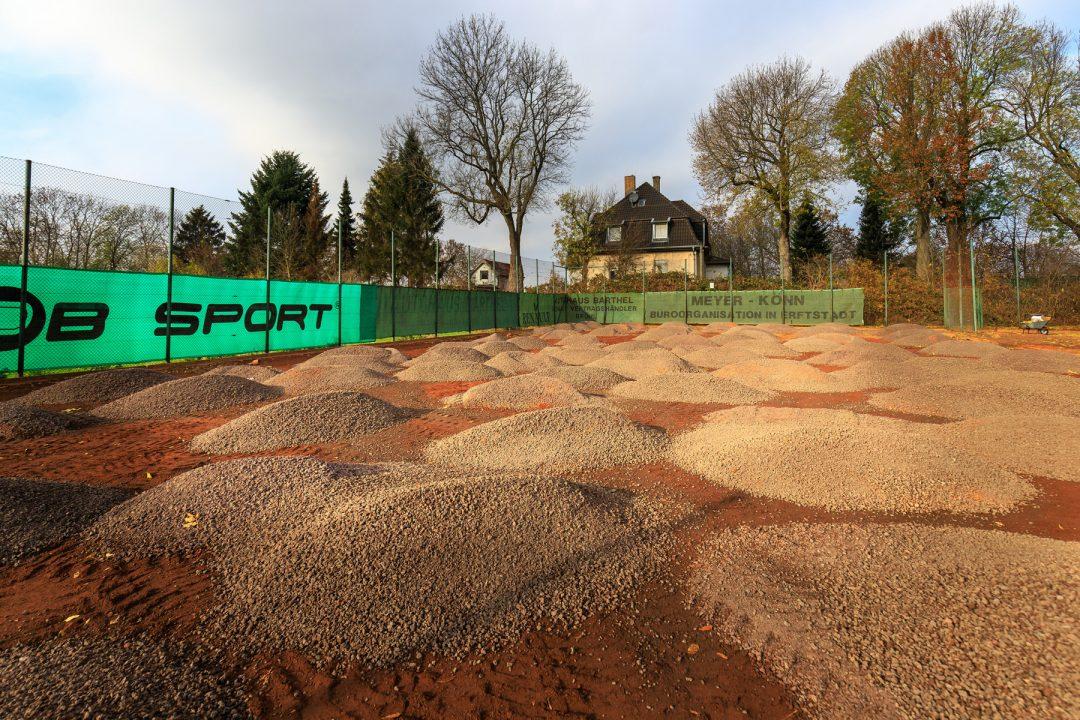 Mehrere Haufen Sand auf einem Tennisplatz