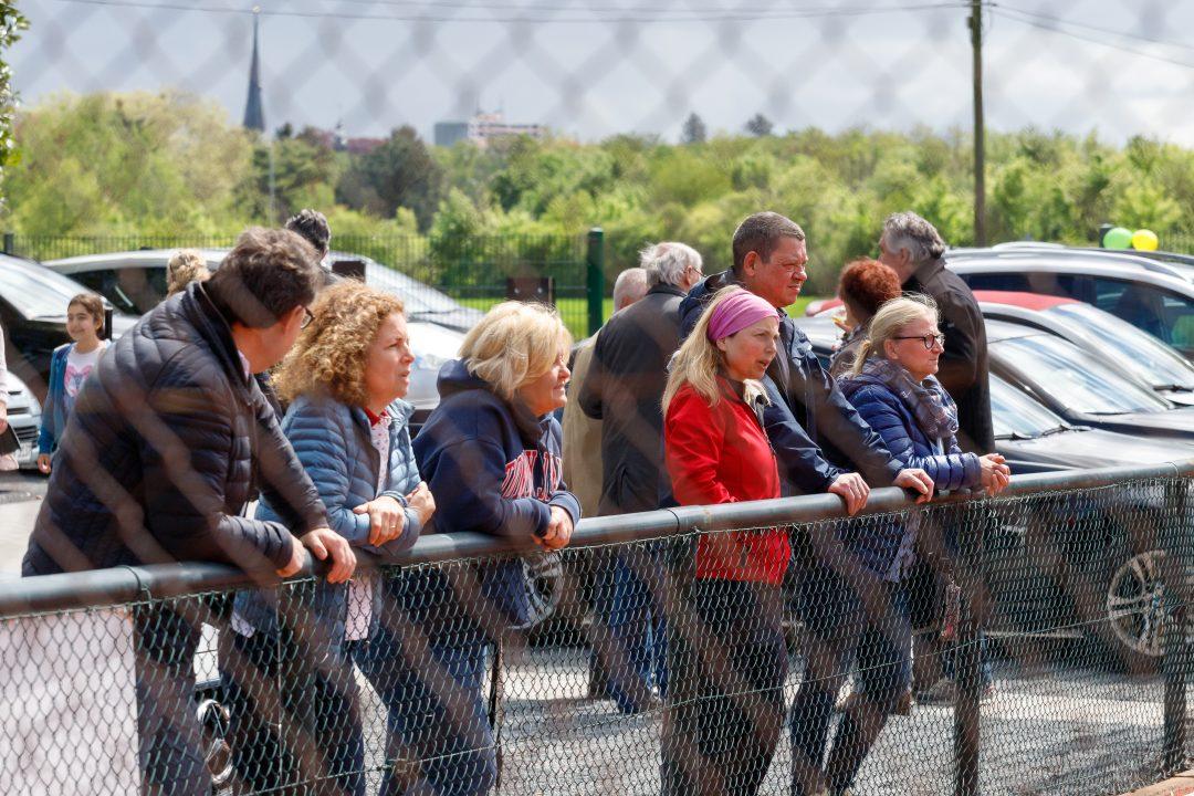 Mehrere Menschen schauen über einen Zaun
