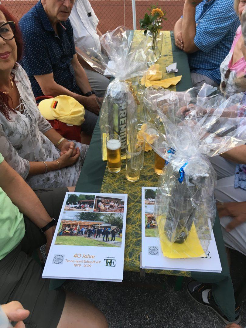 Mehrere Personen mit Geschenken an einem Tisch sitzend