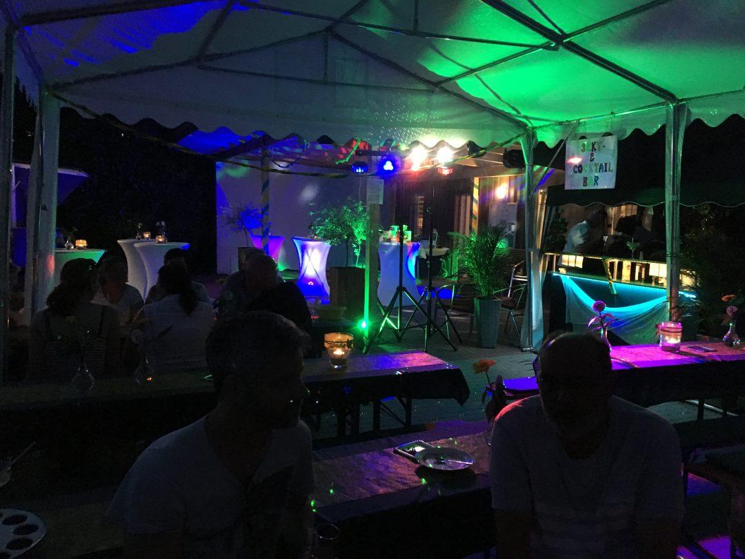 Ein bunt beleuchteter Pavillon mit Bierbänke und Menschen