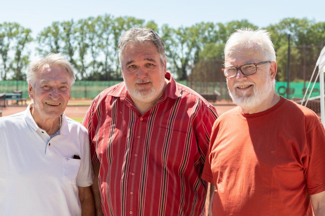 3 Männer in der Sonne vor einem Tennisplatz