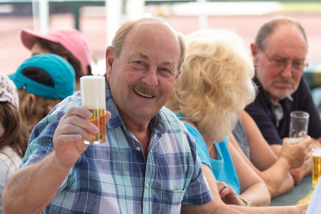 Mann hält Bierglas in Richtung Kamera