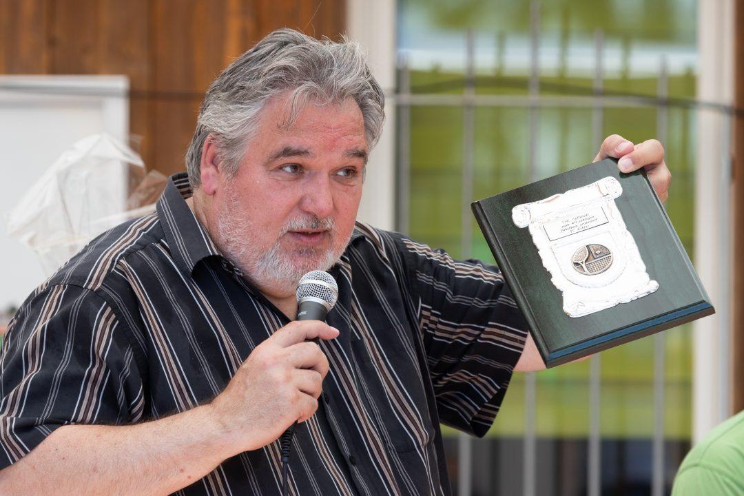 Mann mit Mikrofon überreicht Urkunde