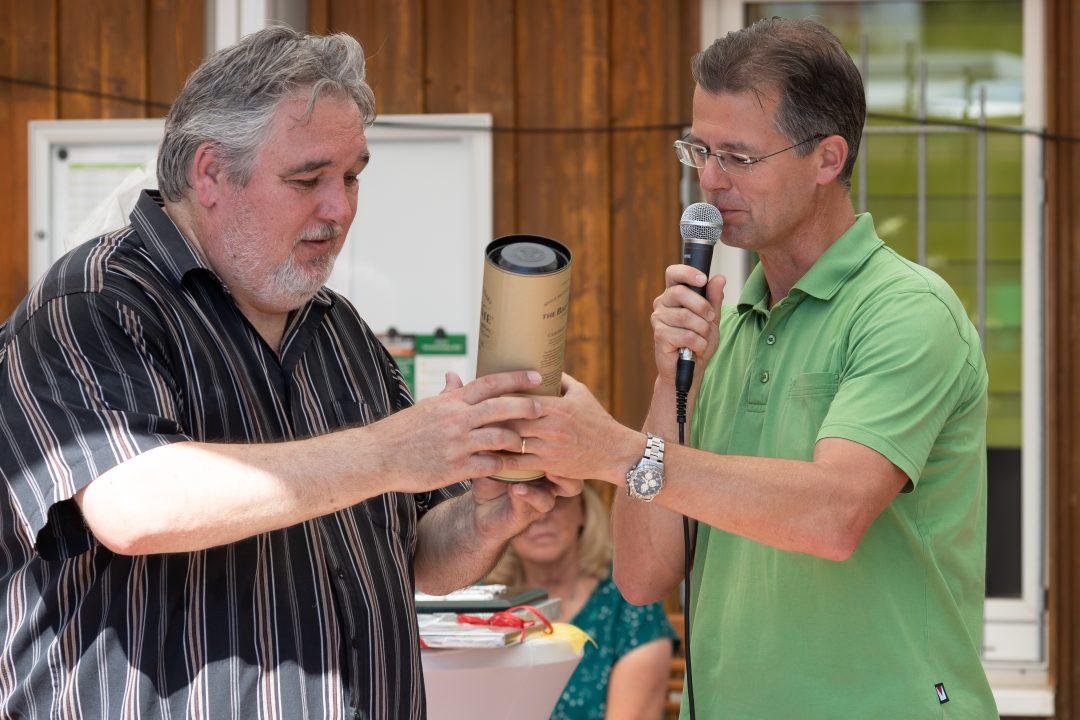 Mann übergibt eine Flasche an einen anderen