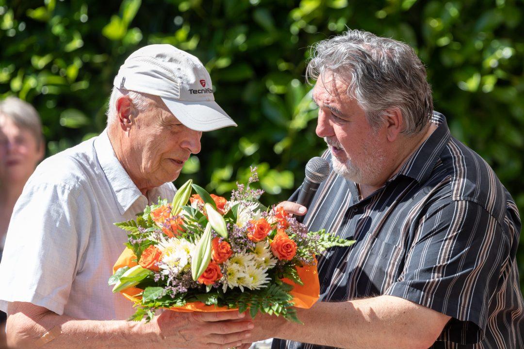 Ein Mann übergibt einen Blumenstrauß an einen anderen