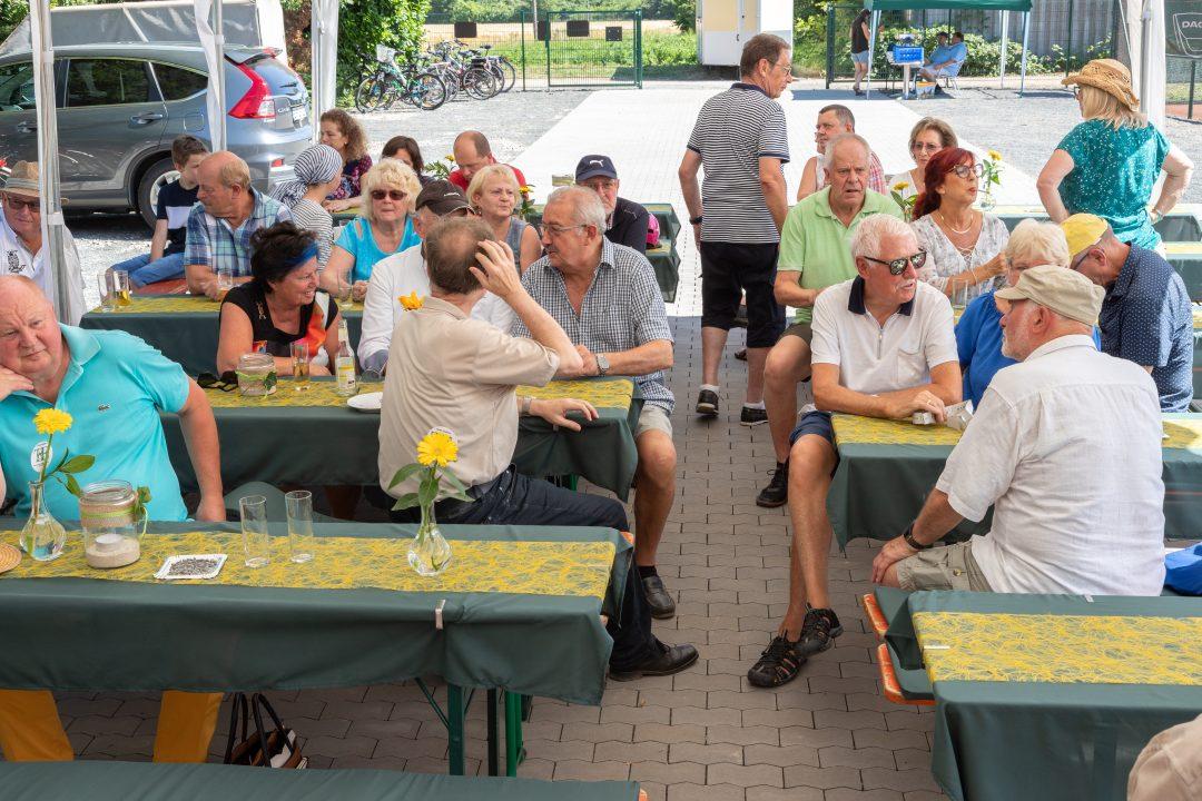 Mehrere Menschen sitzen an einem Biertisch