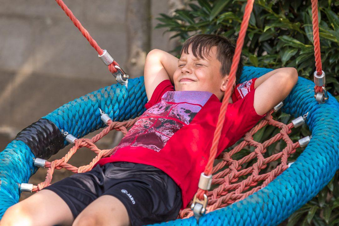 Ein Kind auf einer Liegeschaukel