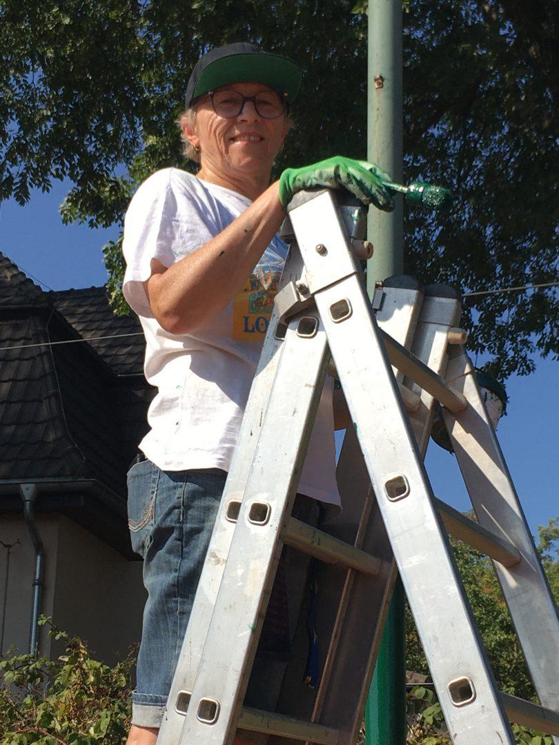Menschen mit Pinsel auf einer Leiter
