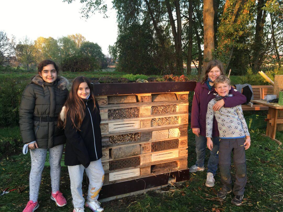 Kinder vor einem Bienenhotels