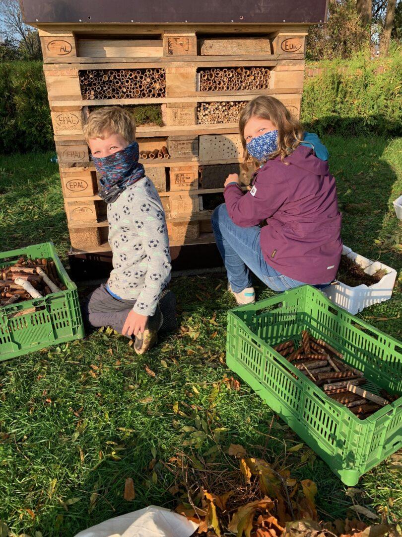 2 Kinder vor einem Bienenhotel
