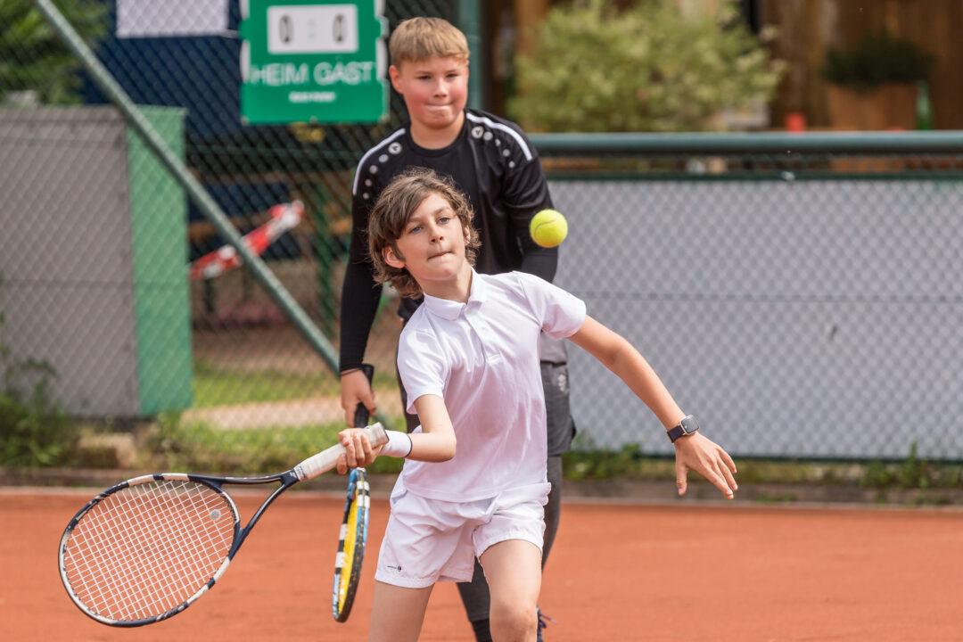 Ein Junge schlägt den Ball konzentriert mit der Vorhand.