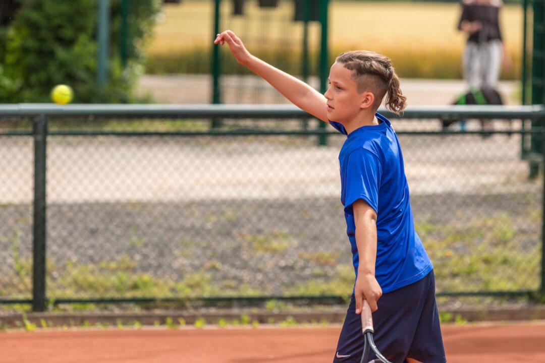 Ein Junge in einem blauen Trikot nach einem Schlag.