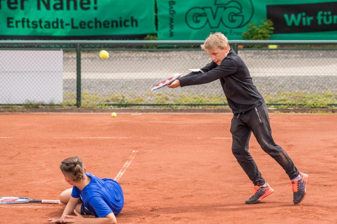 Ein Junge liegt auf dem Boden. Ein anderer schlägt einen Ball mit der Vorhand.