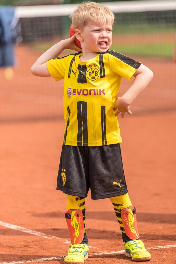 Ein Junge in einem Fußballtrikot wirft einen großen Ball.
