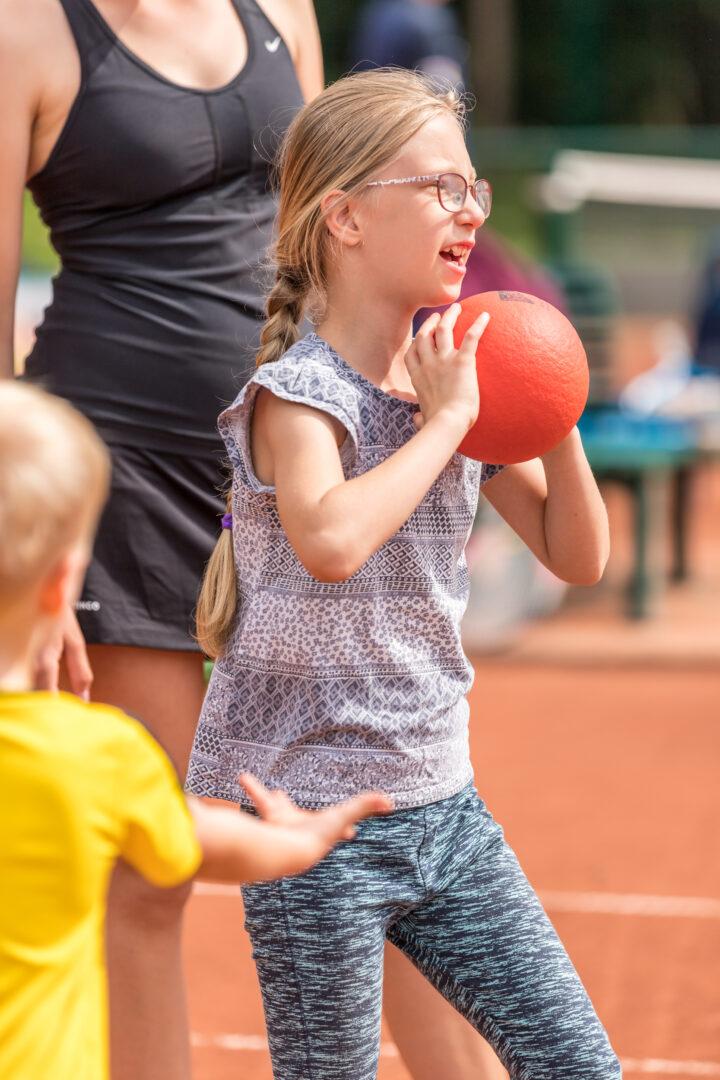 Ein Mädchen hält einen großen Ball in den Händen.