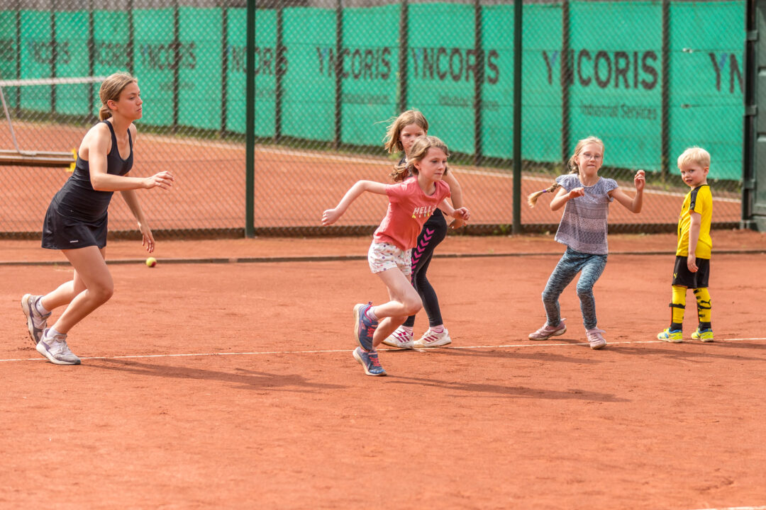 Drei Mädchen rennen um die Wette. Ein Betreuerin rennt mit.