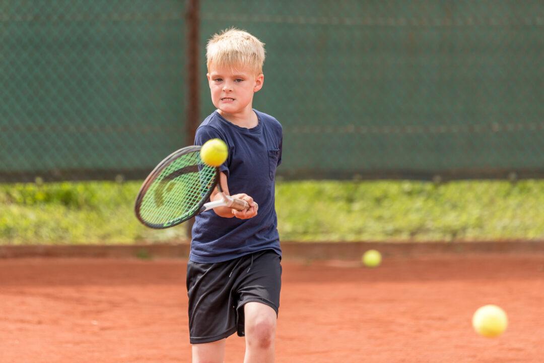 Ein Junge schlägt den Ball mit der Vorhand.