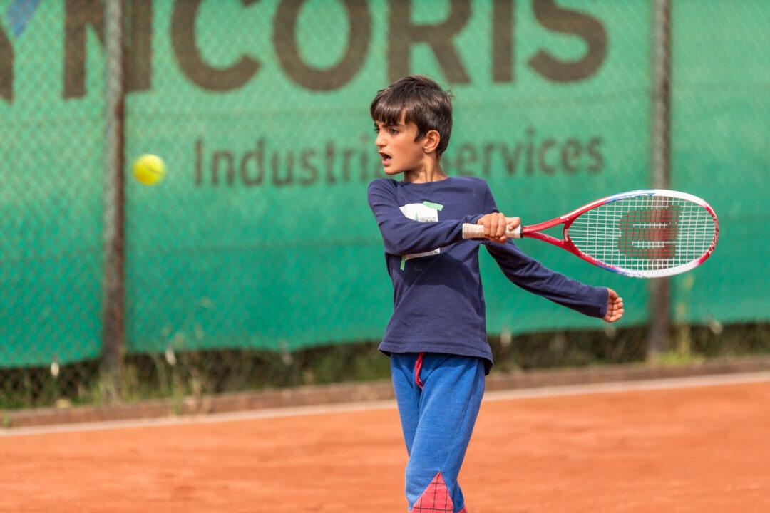 Ein Junge schlägt den Ball kräftig mit der Vorhand.