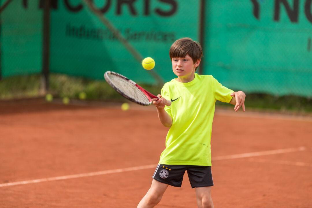 Ein Junge jongliert einen Tennisball mit dem Schläger.